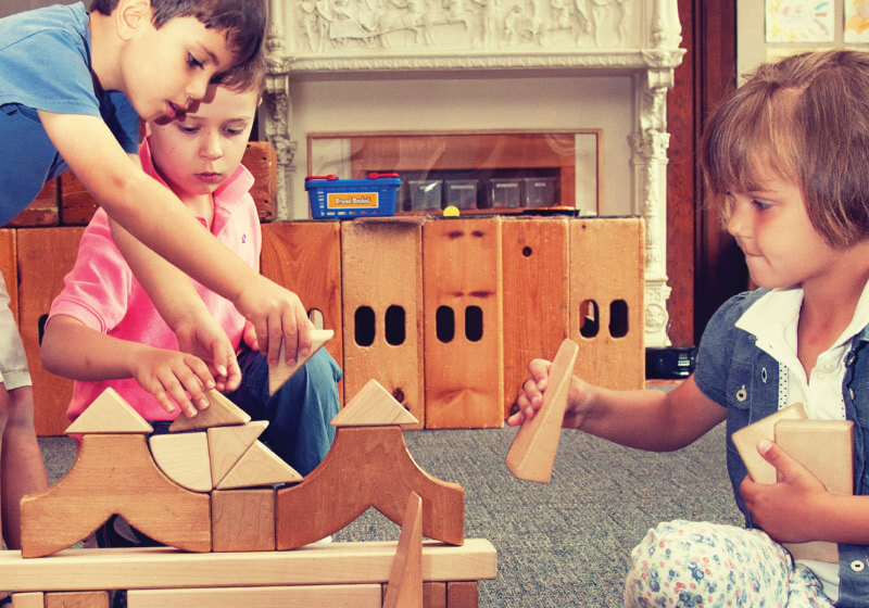 Three children building with wooden blocks